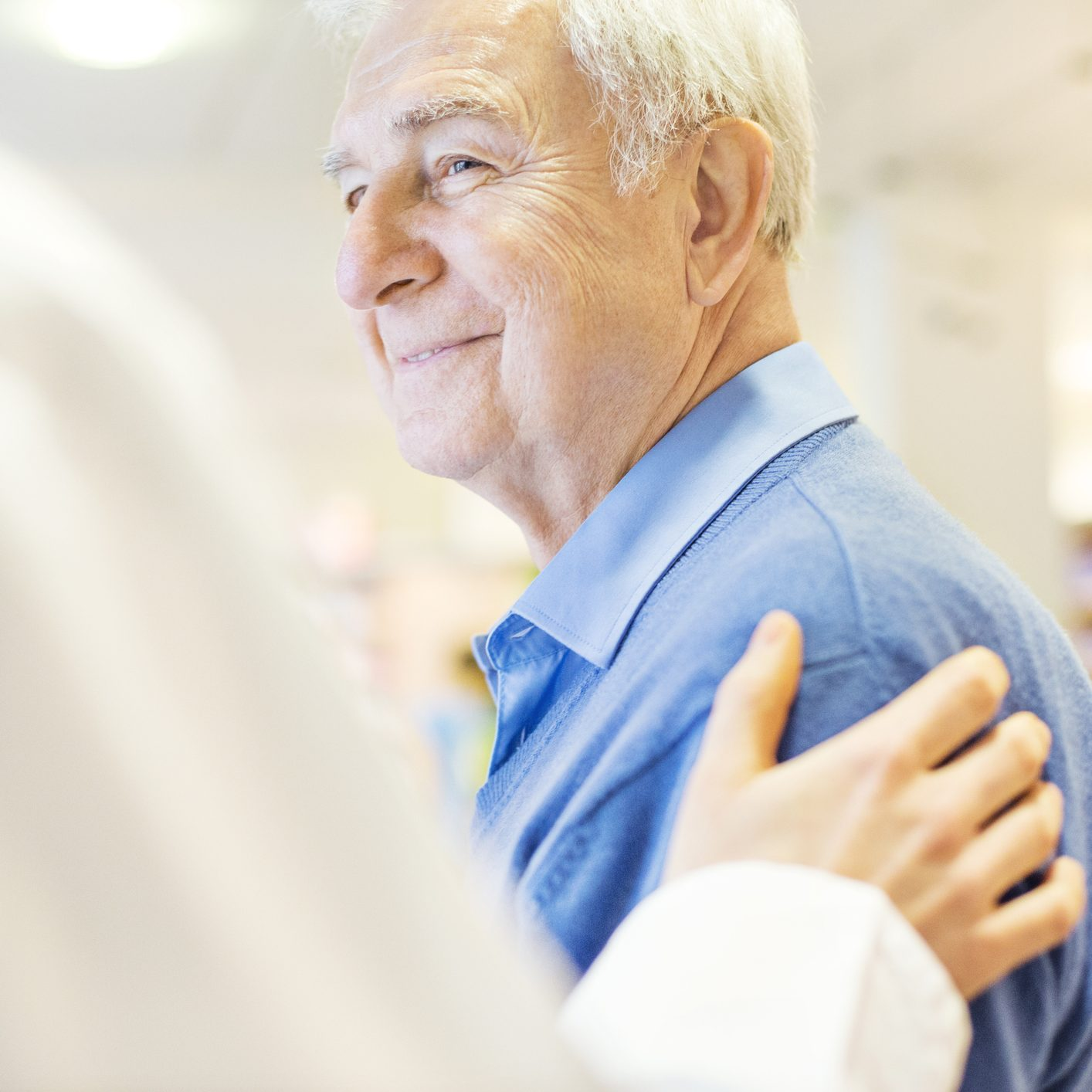Cropped image of female pharmacist consoling senior man in store. Smiling male customer is looking at chemist. They are at brightly lit pharmacy.