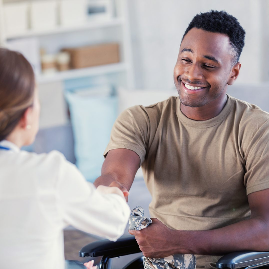 A grateful, wheelchair bound, African American male military veteran smiles and shakes hands with his unrecognizable therapist.
